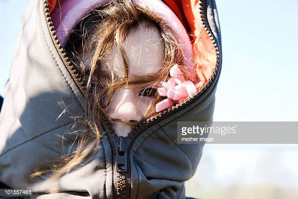 Girl in winter coat zippered all the way up