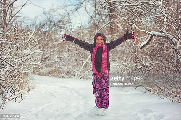 girl in winter wonderland with arms outstretched