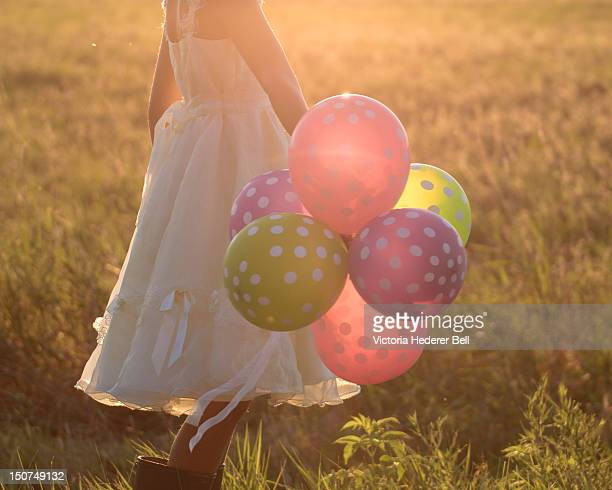 Girl in yellow dress holds bunch of balloons