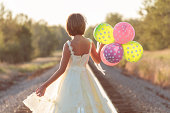 Girl in yellow dress with a bunch of balloons