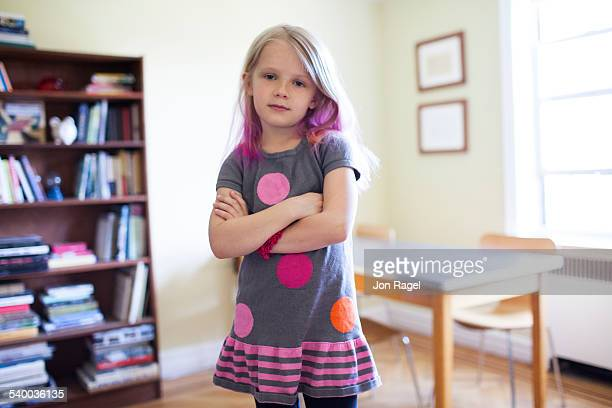 girl indoors with arms crossed