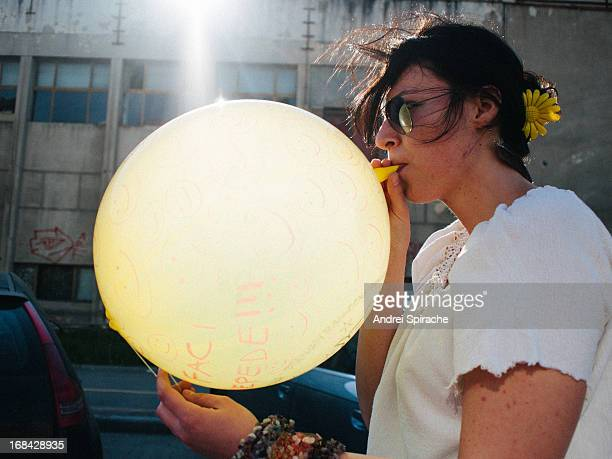 Girl inflating an yellow balloon