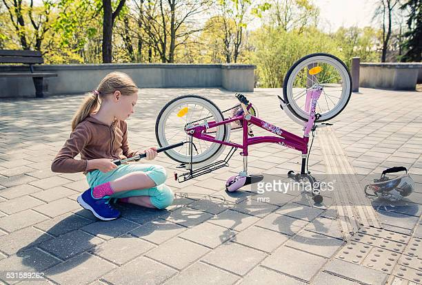 Girl inflating bicycle tire