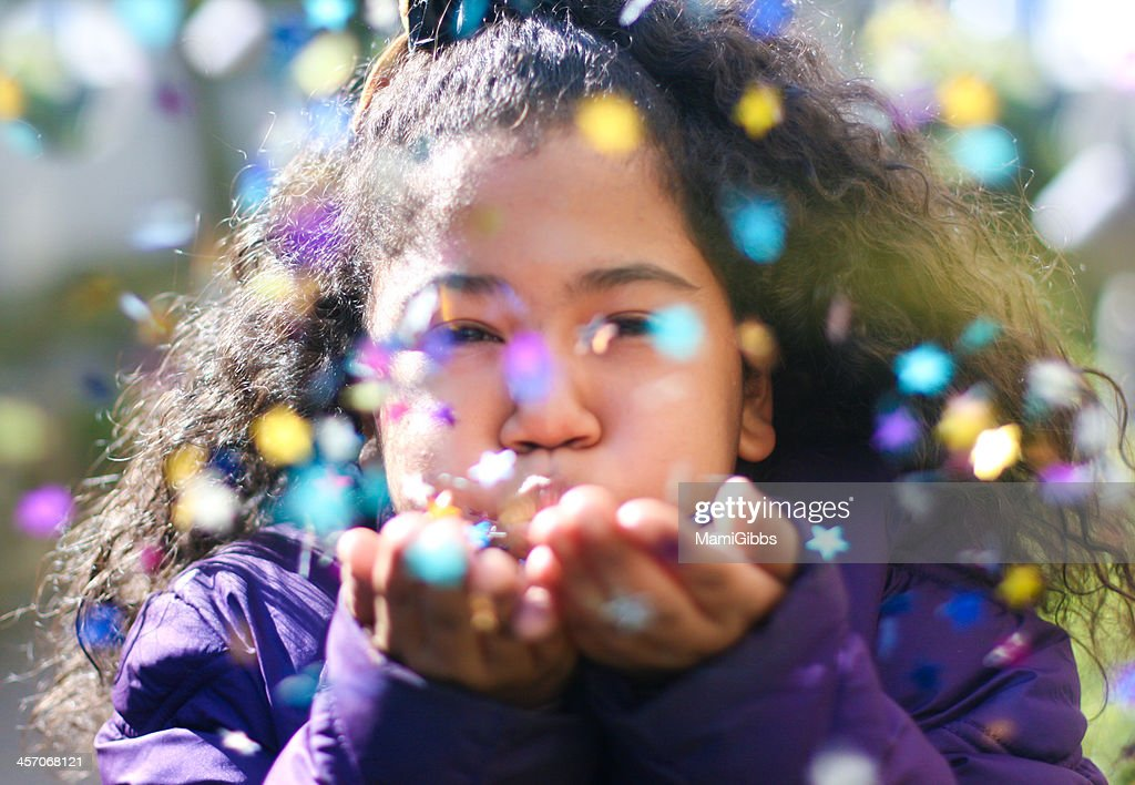 Girl is blowing colorful spangles.