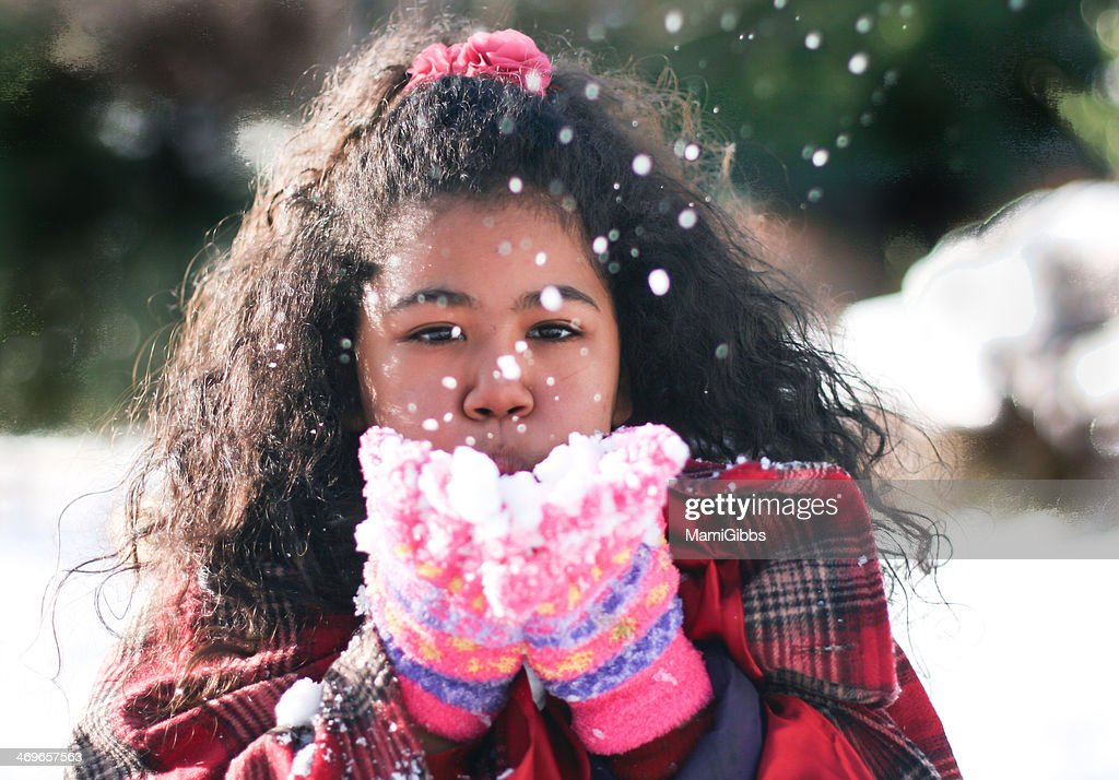 Girl is blowing petal of snow : Stock Photo