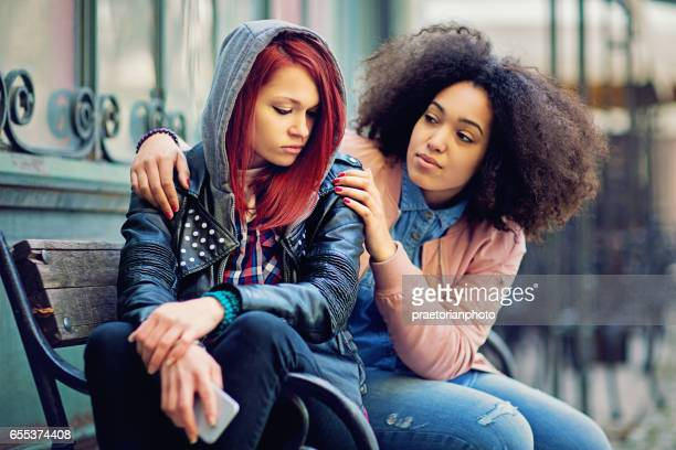 Girl is consoling her girlfriend after break up