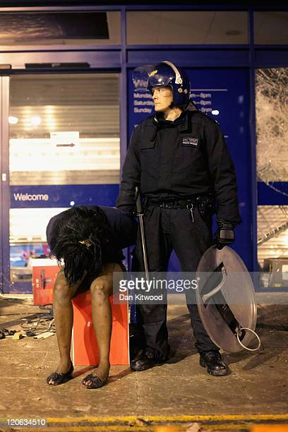 A girl is detained outside the Currys electrical store in Brixton on August 8 2011 in London England Widespread rioting and looting took place across...