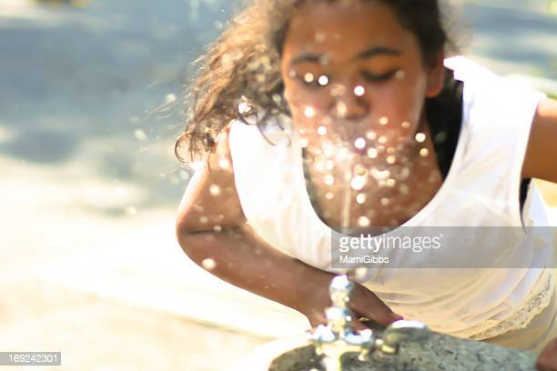 Girl is drinking at public water fountain