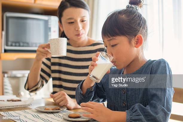 Girl is drinking milk with mother