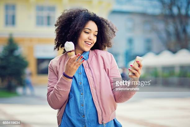 Girl is eating ice cream and looking her mobile phone