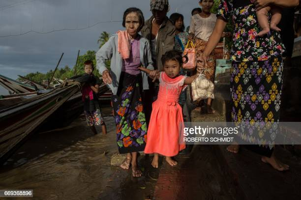 A girl is helped by family members before she and her family boarded a boat that would take them to the Kyauktan Ye Le Pagoda a Buddhist temple built...
