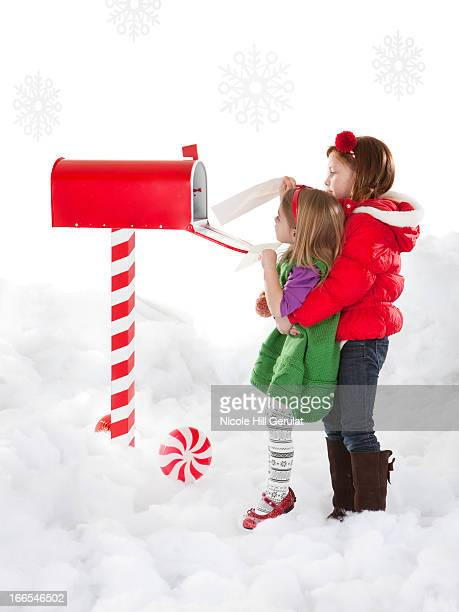 Girl (4-5) is helping sister (18-23months) to send letter