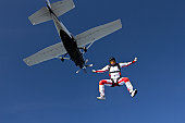 Girl is jumping out of a plane into freefall.