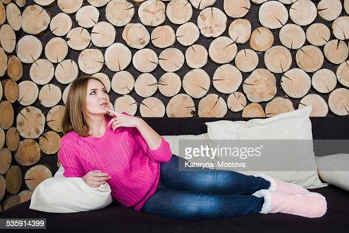 Menina é pôr no sofá em fundo de madeira : Foto de stock