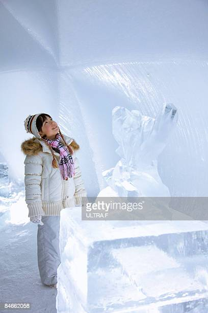 A girl is looking at the wall of ice.