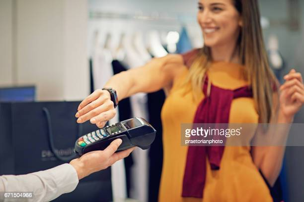 Girl is paying using her smart watch in the Mall