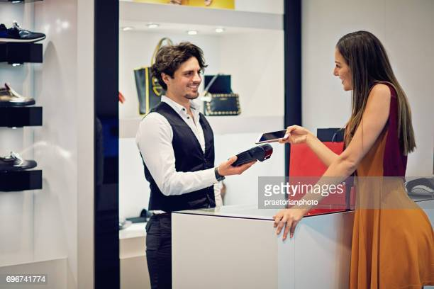 Girl is paying using mobile phone in a boutique