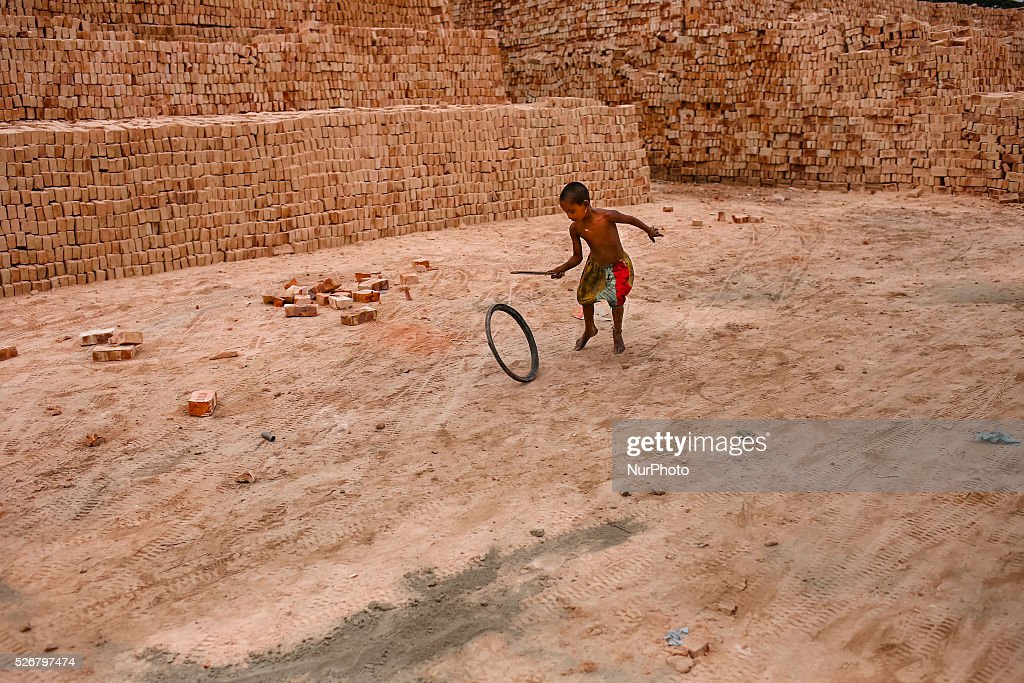 A girl is playing with a bicycle tyre in a brickfield. Brickfield is a place where hundreds of children live with their working parents and growing up here in dusty environment and without any kind of formal education which is leading them towards uncertain future.