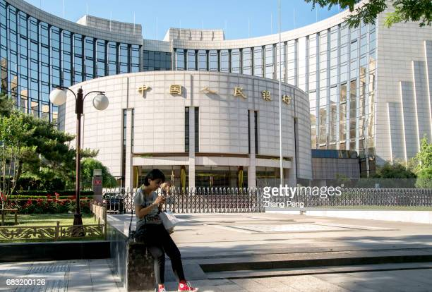 A girl is reading mobile phone on the small square in front of PBoC To offer a longtime and sustainable financial support for the 'One belt One road'...