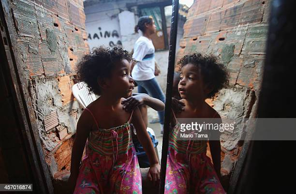 A girl is reflected in a mirror in an impoverished section of the occupied Complexo da Mare one of the largest favela complexes in Rio on October 10...