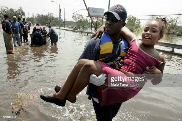 A girl is rescued by a firefighter from New Orleans Frie Department after being trapped in her home in high water in Orleans parish during the...