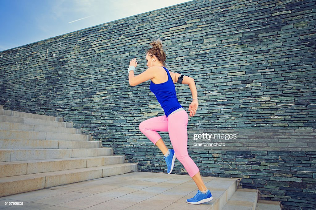 Girl is runing on the city stairs : Stock Photo