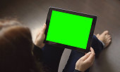 Girl is sitting on the floor and holding a tablet pc with green screen and markers, making pick gestures on touchpad, 4K
