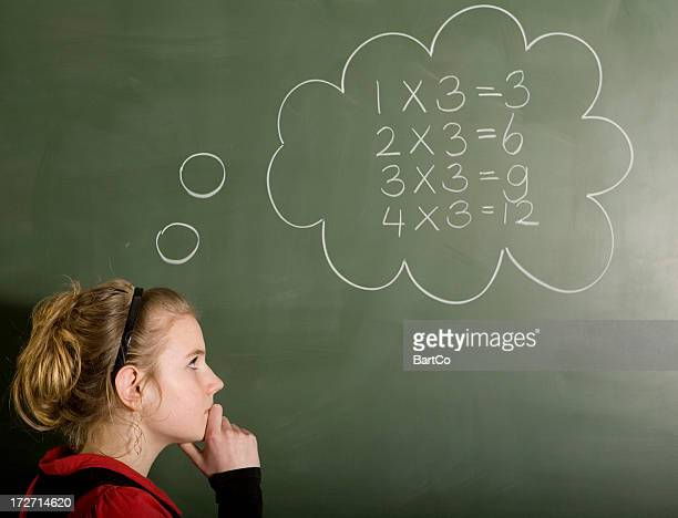 Girl is solving a mathematical problem on blackboard