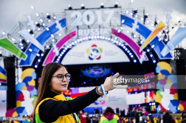 A girl is taking selfie in front of the main scene during the Grand Opening Ceremony of 19th World Festival of Youth and Students in Bolshoy Sports...