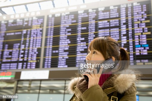 A girl is talking on the phone in the airport.