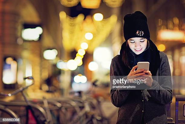 Girl is texting on the front of the Chrismas decoration