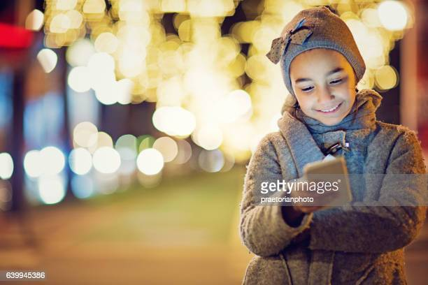 Girl is texting on the front of the city lights