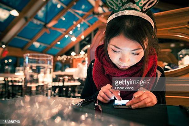 A girl is using smartphone in a restaurant