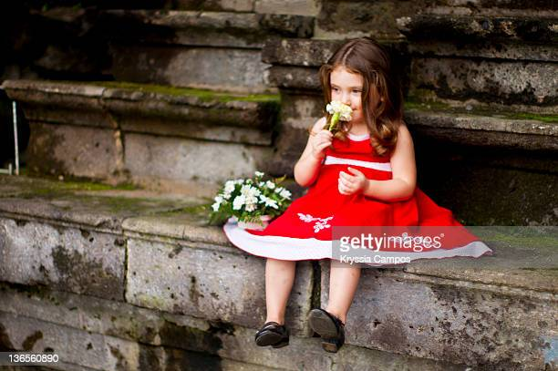 Girl is wearing red dress and she is smeling flowe