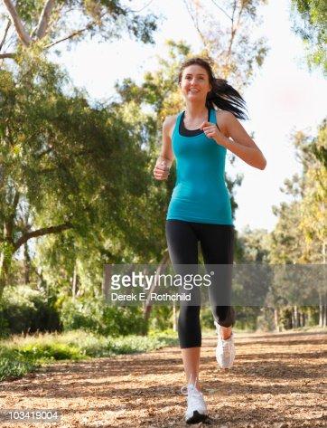 Girl jogging on tree lined path 2 : Bildbanksbilder
