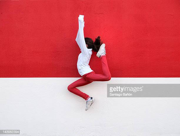 Girl jumping against wall