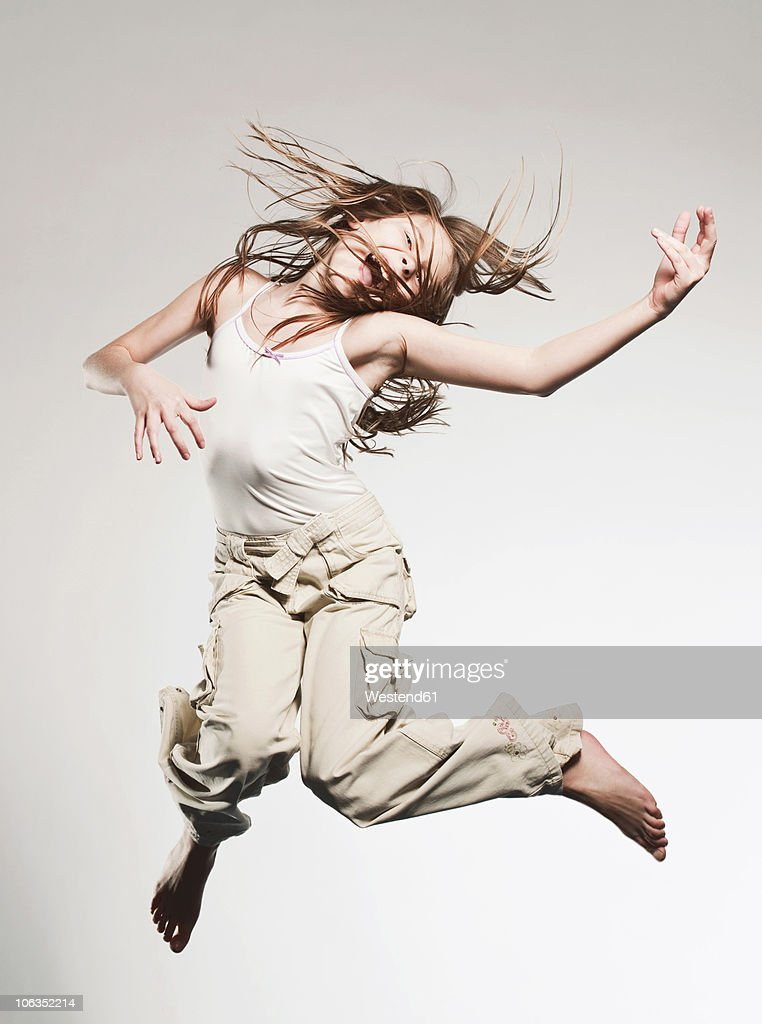 Girl (10-11) jumping and playing airguitar