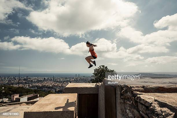 Girl jumping and practicing parkour in the city