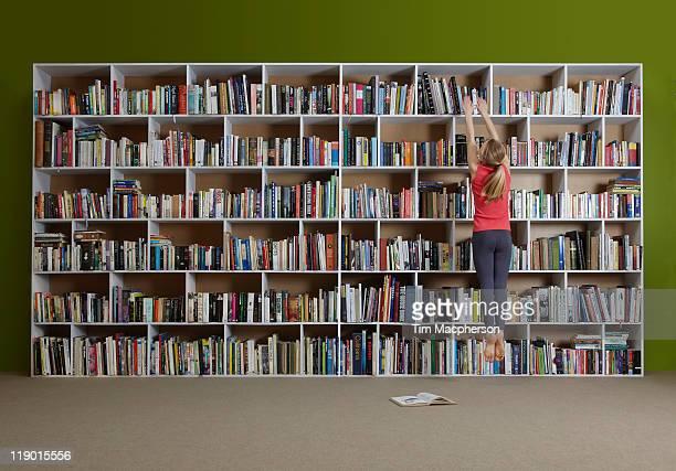 Girl jumping for book on high shelf