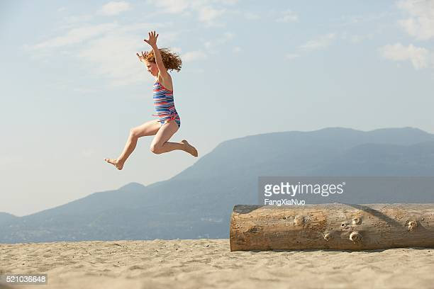 Girl jumping from a log on the beach