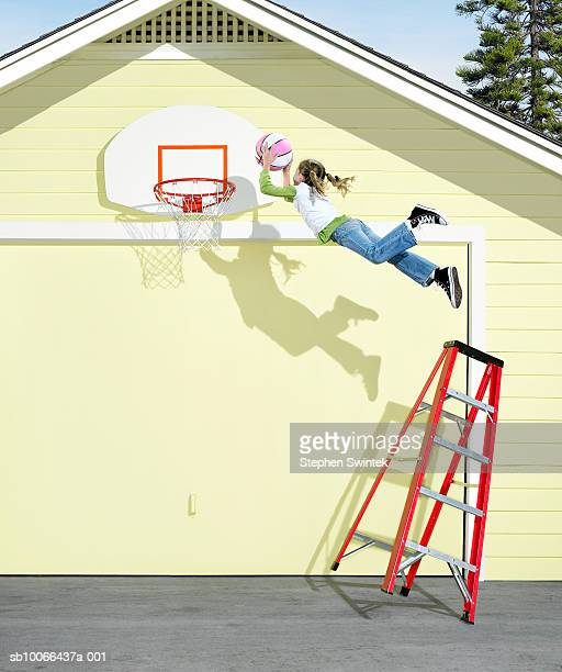 Girl (8-9) jumping from top of ladder attempting to slam dunk basketball (Digital Composite)