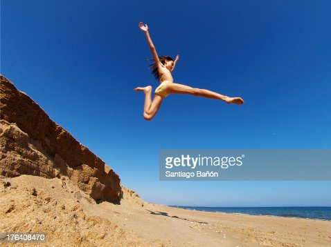 Girl jumping high in the air at beach
