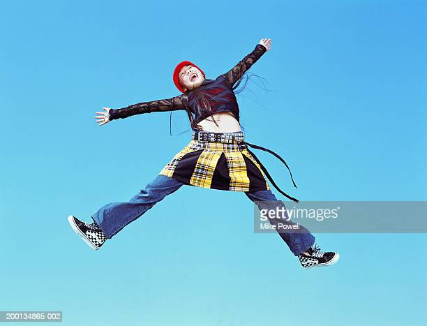 Girl (12-14) jumping in air, arms outreached, low angle