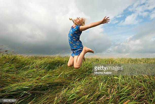 Girl jumping in field of tall grass
