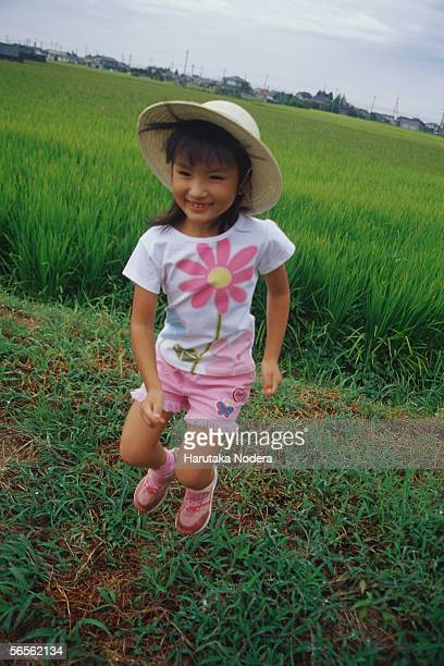 Girl jumping in front of rice paddy