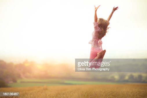 Girl Jumping in Harvested Wheat Field : ストックフォト