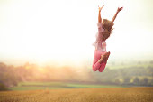 Girl Jumping in Harvested Wheat Field