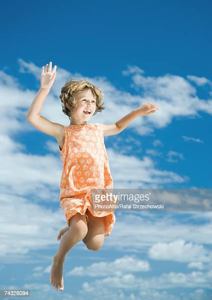 Girl jumping in mid air, sky in background