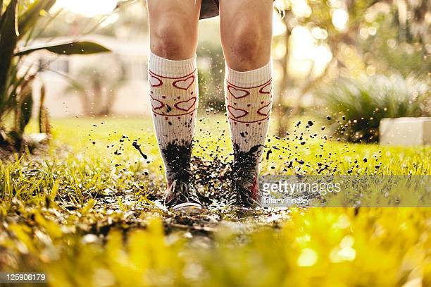 Girl jumping in mud splash