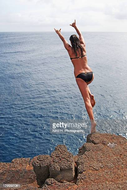 Girl jumping in ocean, Naalehu, Big Island